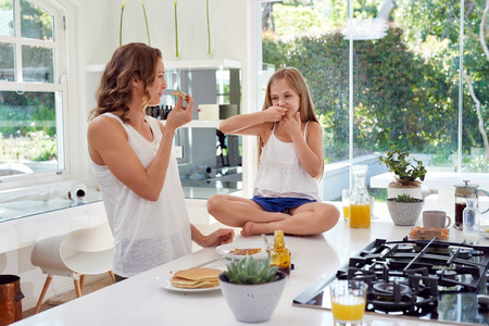 messy kitchen: Happy, smiling mother and daughter eating fresh homemade pancakes having fun in contemporary modern kitchen house Stock Photo
