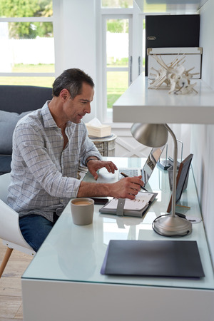 business man working at home office with laptop and writing on notebook Standard-Bild