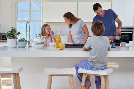 rodina: usměvavé Kavkazská rodina v kuchyni připravuje snídani Reklamní fotografie