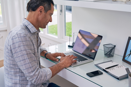 business man entrepreneur working on laptop from home office space
