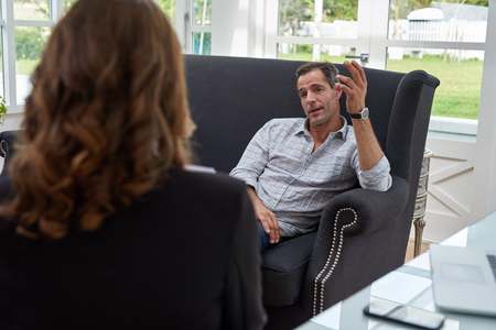 Female psychologist consulting mature man during therapy session