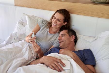 marido y mujer: Feliz pareja madura sonriente marido esposa en busca de telefonía celular móvil al tiempo que sienta en la cama