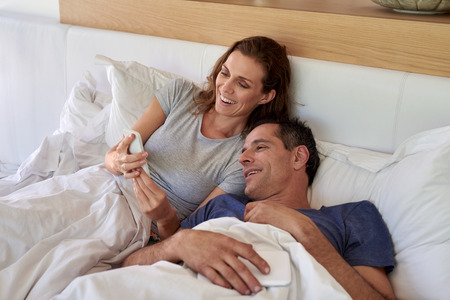 husband and wife: Happy mature smiling husband wife couple looking at mobile cell phone while laying in the bed