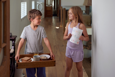 Smiling caucasian brother and sister siblings carrying surprise mothers day breakfast tray