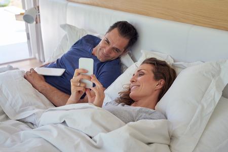pareja en la cama: caucásica sonriente pareja, marido y mujer tumbada en la cama con un dispositivo de tableta y teléfonos inteligentes en el fin de semana por la mañana