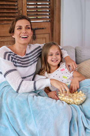 snuggling: Beautiful Caucasian mother and child kid spending quality time sitting on sofa at their home eating popcorn and watching tv snuggling under blanket Stock Photo