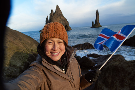 icelandic flag: happu independent woman traveller at black sand beach south iceland, taking a selfie at reynisdrangar stone sea stacks, waving icelandic flag