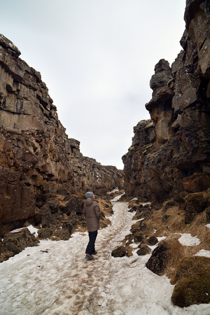 scenary: Independent Tourist walking through the crack between tectonic plates in Thingvellir national park, Iceland