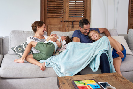семья: Счастливый возбужденных дети брат и сестра, прыжки и играть с родителями на диване в гостиной Фото со стока