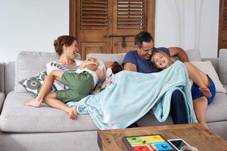 familia feliz casa: niños emocionados feliz hermano y hermana saltando y jugando con los padres en el sofá de la sala de estar Foto de archivo