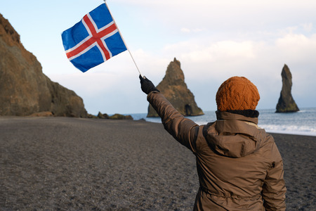 icelandic flag: Independent traveller at black sand beach south iceland, looking at reynisfjara stone sea stacks, waving icelandic flag