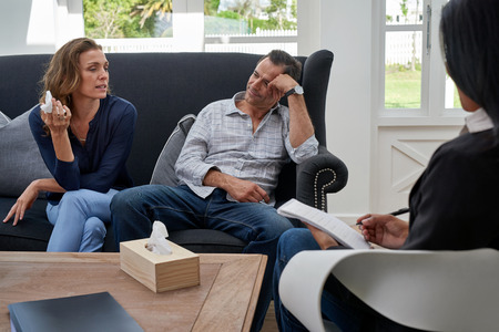 therapist: mature couple seated on couch, woman crying during therapy session Stock Photo