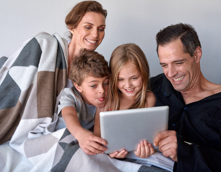 device: Happy caucasian family with two kids spending quality time internet video call on tablet device at home Stock Photo