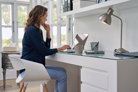 office space: businesswoman entrepreneur working on laptop from home office space Stock Photo