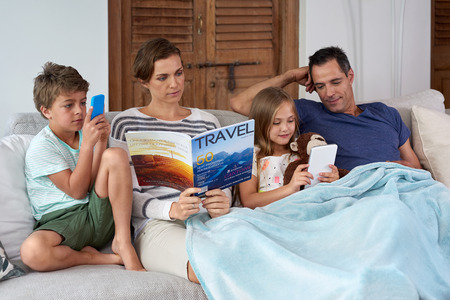device: Caucasian family relaxing at home mom reading magazine kids playing games on tablet device and mobile cell phone