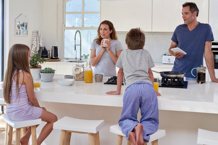 happy smiling caucasian family in the kitchen having breakfast