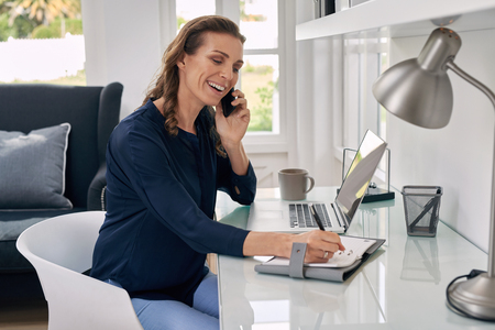 talking: Casual businesswoman working remotely from home office writing on notepad and talking on mobile phone.