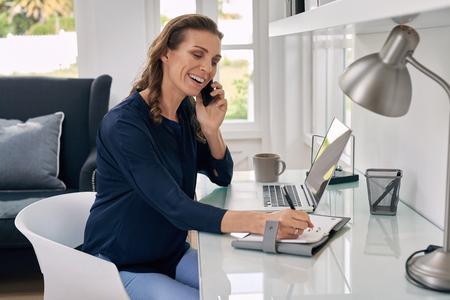 Mulher de neg�cios ocasional que trabalha remotamente a partir de escrita escrit�rio em casa no bloco de notas e falando no telefone m�vel.