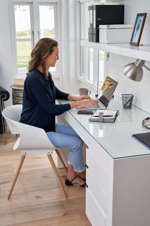 businesswoman entrepreneur working on laptop from home office space 스톡 콘텐츠