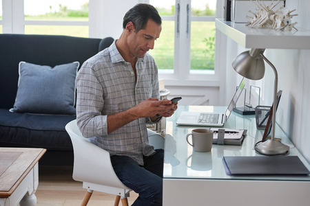 Mature handsome man looking at mobile cell phone while at home in office work space Banque d'images