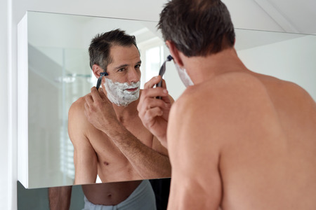routine: Mature Caucasian man shaving in modern bathroom at home using a razor Stock Photo