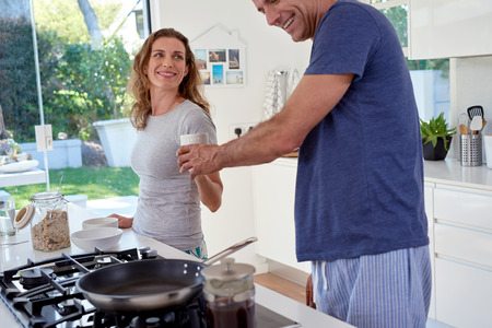 breakfast cup: successfulcouple in kitchen, man giving beautiful woman a cup of tea coffee during breakfast morning Stock Photo