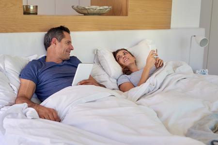Esposas: caucásica sonriente pareja, marido y mujer tumbada en la cama usando el dispositivo de tableta y el smartphone Foto de archivo