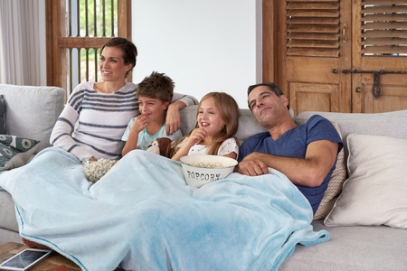Happy laughing Caucasian family with two children relaxing at home, kids brother and sister watching a movie and having popcorn with parents