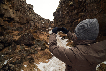 tourist tourists: Tourist taking photso of the crack between tectonic plates in Pingvellir national park Iceland