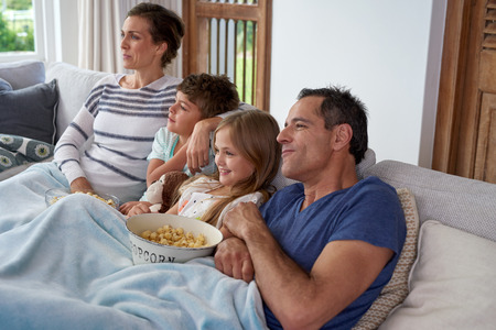 Happy Caucasian family with two children relaxing at home, kids brother and sister watching a movie and having popcorn with parents