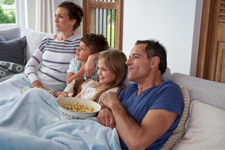 cine: Familia cauc�sica feliz con dos hijos de relax en casa, ni�os hermano y hermana viendo una pel�cula y palomitas de ma�z que tiene con los padres