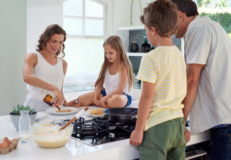 Happy caucasian family standing around stove, kitchen counter putting syrup on pancakes