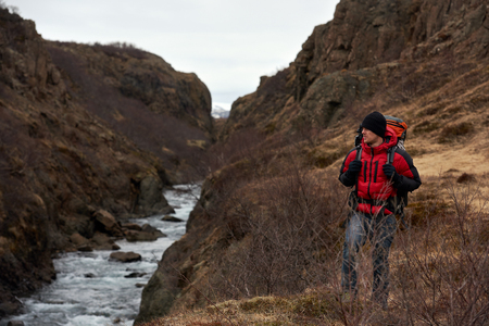 destination scenic: Man on solo camping trip with backpack and winter gear walking along fast flowing rocky river, in scenic outdoor nature destination