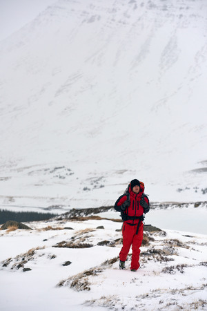 full red: Man in full red winter gear and backpack hiking in the snow exploring the all white natural landscape