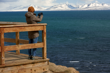 scenary: Tourist standing on wooden lookout point deck taking a photo of the beautiful coastal scenary with snow capped mountains in background Stock Photo