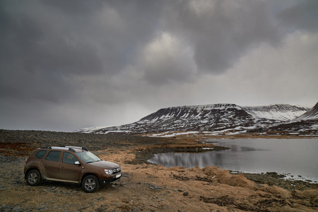 adventure holiday: 4x4 parked at a viewpoint, overlooking lake in winter landscape in iceland, roadtrip adventure holiday