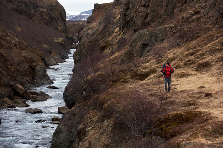 destination scenic: Man hikes alone with backpack and winter gear walking along fast flowing rocky river, in scenic nature destination