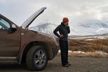 Aziatische vrouw met huren autopech motorpech met kap omhoog, bellen met mobiele telefoon om hulp, gestrand in de winter