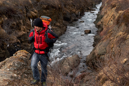rugged terrain: Man in winter gear emerges from gorge  with backpack walking from the fast flowing rocky river, in scenic nature destination Stock Photo