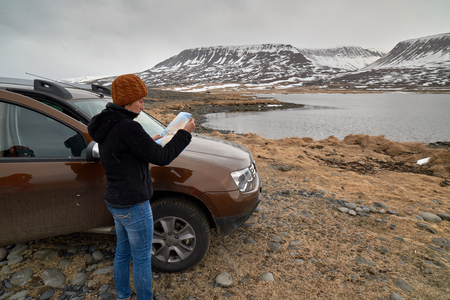adventure holiday: Woman traveler steps out of 4x4 rental car on holiday and looks at map, solo adventure roadtrip holiday Stock Photo
