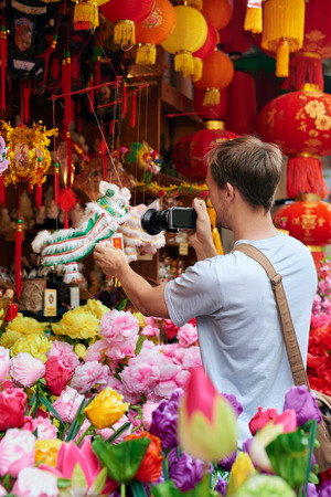 hongkong: Solo traveler tourist taking photos of traditional cultural lion dance souvenir shop store decorations for chines new year in modern asian city
