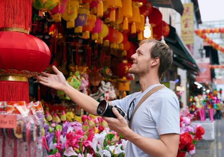 Podróżnik Turysta z aparatem w nowoczesny azjatyckiego miasta chinatown zakupy patrząc na czerwoną latarnią na drobiazgi z pamiątkami Zdjęcie Seryjne