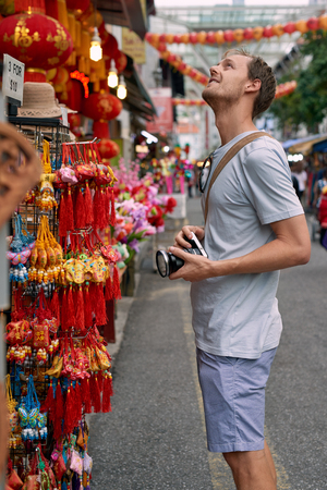 trinkets: Tourist traveler with camera in asian city chinatown exploring cultural attractions and shopping for souvenir trinkets Stock Photo