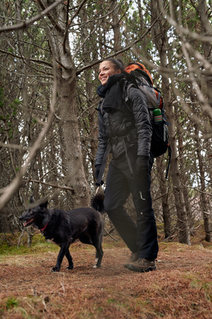 companion: Happy active lifestyle woman walking hiking trekking in forest woods with best friend companion pet dog