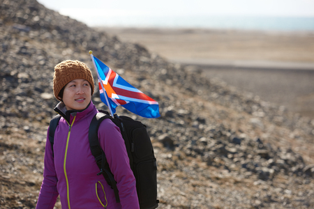 stark: Woman traveller exploring hiking in stark icelandic landscape the iceland flag flapping in the wind