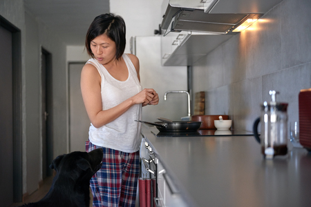 asia women: asian woman talks to her pet labrador dog while she stands by the kitchen stove cooking, loving pet owner relationship