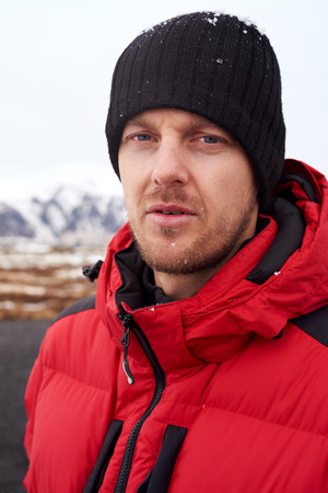 rugged man: Portrait of outdoors sporty rugged adventure man with puffy jacket and beanie, in cold extreme winter weather