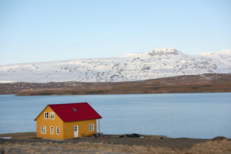 quaint: Quaint cottage home house in iceland, overlooking water fjord and snowy mountains in distance
