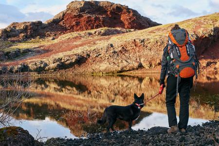 배낭과 애완견이 아름다운 호수 너머로와 하드 인상 후보기를 즐기는 여자