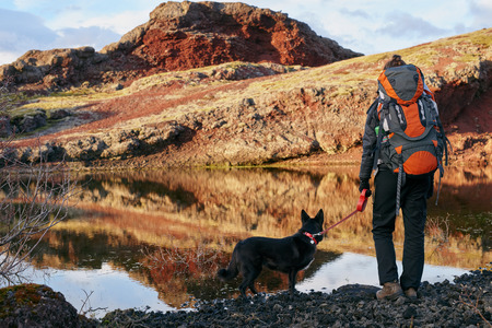 Woman with backpack and pet dog looking over the scenic lake and enjoying the view after a hard hike